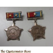 Stamped white medal five-pointed faceted star with loop for ribbon suspension; the face with a circular central medallion with gilded stippled ground, the flag of the Provisional Revolutionary Government of the Republic of South Vietnam (Vietcong) in red,